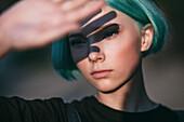 Close-up of teenage girl shielding eyes on sunny day