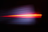 Close-up of abstract red light trail against black background