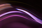 Full frame abstract image of purple light trails against black background