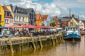 Pavement café and fish restaurants at the pier, inner harbour of the coastal town Husum at the North Sea, Germany.