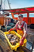 Fisherman with fish, Gager, Moenchgut, Ruegen Island, Mecklenburg-Western Pomerania, Germany