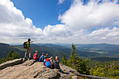 Mountain guide with a group of children, view from Grosser Arber over Lamer Winkel, Bavarian Forest, Bavaria, Germany