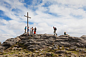 Hiker at the summit cross, Grosser Arber, Bavarian Forest, Bavaria, Germany