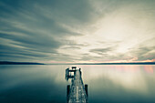 jetty with a bench and dramatic sky, lake Ammersee, Bavaria, Germany