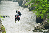 Rescue dog and mountaineer on a flying fox, river Salzach, Austria
