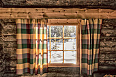 view out of the window of a cosy log cabin  onto the snowscape, Luosto, finnish Lappland