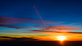 contrail of an airplane in a higher flightlevel gets illuminated in orange color during a sunsetflight above France