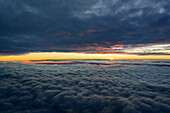 aerial image of a sunset between two cloud-layers