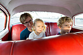 mother with children, sitting in a red oldtimer, comfortable seating, historic town center, old town, Habana Vieja, family travel to Cuba, parental leave, holiday, time-out, adventure, MR, Havana, Cuba, Caribbean island