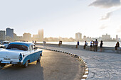 Blue oldtimer, driving along Malecon, historic town center, old town, Habana Vieja, Habana Centro, family travel to Cuba, holiday, time-out, adventure, Havana, Cuba, Caribbean island
