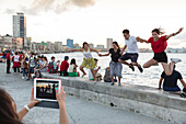 tourists and local people and fisherman at Malecon, woman taking pictures with tablet, historic town, center, old town, Habana Vieja, Habana Centro, family travel to Cuba, holiday, time-out, adventure, Havana, Cuba, Caribbean island