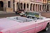 Pink oldtimer, cabriolet, driving along Malecon, taxi, historic town, center, old town, Habana Vieja, Habana Centro, family travel to Cuba, holiday, time-out, adventure, Havana, Cuba, Caribbean island