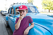 boy standing in front of a blue oldtimer, pretending to smoke a cigarette, at park Parque Jose Marti in the center of Cienfuegos, colonial town, family travel to Cuba, parental leave, holiday, time-out, adventure, MR, Cienfuegos, Cuba, Caribbean island