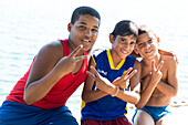 Three young local boys along the shore, victory sign, Cienfuegos, Cuba, Caribbean island