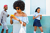 young cool people on their mobile, taking a rest, school uniform, family travel to Cuba, parental leave, holiday, time-out, adventure, Trinidad, province Sancti Spiritus, Cuba, Caribbean island