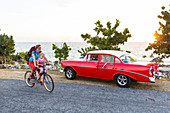 red oldtimer, woman with kid cycling along the lonely coast road from La Boca to Playa Ancon, with beautiful small beaches in between, turquoise blue sea, family travel to Cuba, parental leave, holiday, time-out, adventure, MR, La Boca, Trinidad, Cuba, Ca