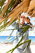 cuban man repairing the roof of a sun shade made from palm trees, lonely coast road from La Boca to Playa Ancon, with beautiful small sandy beaches in between, at the beach, turquoise blue sea, family travel to Cuba, parental leave, holiday, time-out, adv