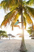 man climbing up a palm tree, lonely coast road from La Boca to Playa Ancon, with beautiful small sandy beaches in between, at the beach, turquoise blue sea, family travel to Cuba, parental leave, holiday, time-out, adventure, MR, near Trinidad and La Boca