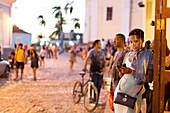 Kubanerin mit Handy, Frau, Schönheit, an den Terrassen von Trinidad an der Iglesia Parroquial de la Santisima Trinidad in der Nähe des Plaza Mayor, auf den Treppenstufen und im Cafe Trinidad Terraces treffen sich Touristen aus aller Welt, beliebter Platz,
