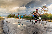 family jumping in puddles after the rain, lonely coast road from La Boca to Playa Ancon, with beautiful small beaches in between, turquoise blue sea, family travel to Cuba, parental leave, holiday, time-out, adventure, MR, near Trinidad, Cuba, Caribbean i