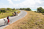 woman with child cycling along the lonely coast road from La Boca to Playa Ancon, with beautiful small beaches in between, turquoise blue sea, family travel to Cuba, parental leave, holiday, time-out, adventure, MR, near Trinidad, Cuba, Caribbean island