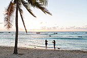 female tourists, women, taking pictures on the beach at sunset, palm tree, lonely coast road from La Boca to Playa Ancon, with beautiful small sandy beaches in between, at the beach, turquoise blue sea, snorkeling, family travel to Cuba, parental leave, h