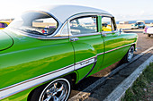 green oldtimer, driving along Castillo De Los Tres Reyes Del Morro, historic town, family travel to Cuba, holiday, time-out, adventure, Havana, Cuba, Caribbean island