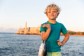6 years old boy with a fish at Malecon, tourists, local people and fisherman at Malecon, historic town, center, old town, Habana Vieja, Habana Centro, opposite Castillo De Los Tres Reyes Del Morro, family travel to Cuba, holiday, time-out, adventure, MR,