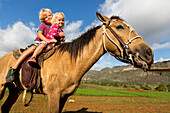 Small children on a horse, horseride, Mogotes and tobacco fields in Vinales, climbing region, loneliness, countryside, beautiful nature, family travel to Cuba, parental leave, holiday, time-out, adventure, MR, National Park Vinales, Vinales, Pinar del Rio