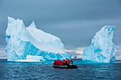 A Zodiac raft and expedition cruise ship MS Bremen (Hapag Lloyd Cruises) are dwarfed by a towering iceberg, Active Sound, Antarctica
