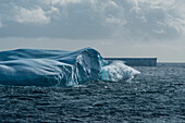 A wave crashes against an iceberg, near Cape Adare, Antarctica