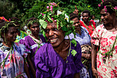 A local woman in a purple dress and headdress of leaves and flowers laughs in the middle of a group of women, Waisisi Bay, Tanna Island, Vanuatu, South Pacific
