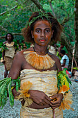 A young woman with traditional clothing made of plant material and a leafy headdress stands in a clearing prior to a cultural performance, Nendo Island, Santa Cruz Islands, Solomon Islands, South Pacific