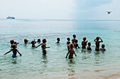 A group of children and teenagers play in the water and look up to watch a DJI Pantom 4 drone flying above, Santa Ana Island, Makira-Ulawa, Solomon Islands, South Pacific