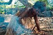 A kneeling woman wearing a traditional grass dress tends her fire during a cultural performance, Arabala, Langa Langa Lagoon, Malaita, Solomon Islands, South Pacific