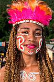 A woman with face-painting, a headdress of feathers and shells and braided hair smiles into the camera prior to a cultural performance, Port Numbay, Jayapura, Papua, Indonesia, Asia