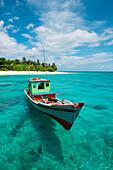 Ein buntes Boot treibt in klarem türkisfarbenen Wasser vor einer Insel, Senua, Indonesien