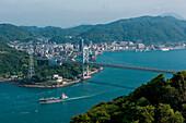Overhead of ship passing underneath bridge and city seen from a vista point, Moji, Fukuoka, Japan, Asia
