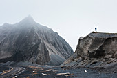 A German tourist takes a photograph from an eroded hill of a craggy, misty mountain near the shoreline, Atlasova Island, Kuril Islands, Russia, Asia