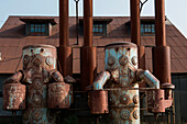 Rusted metal tanks in front of a factory building look almost human, Nome, southern Seward Peninsula, Alaska, USA, North America