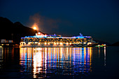 Full moon rises over mountains behind illuminated cruise ship Norwegian Pearl (NCL Cruises) as it leaves the harbor at night, Juneau, Alaska, USA, North America