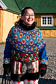 A woman in traditional dress smiles in front of a ocher-colored building with a green roof, Sisimiut, Qeqqata, Greenland