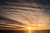 Unusual cloud formations highlight a golden sunset, near Ilulissat (Jakobshavn), Disko Bay, Kitaa, Greenland