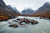 A glacial stream of milky-green water rushes over rocks in a mountainous, autumnal tundra landscape, Dronning Marie Dal (Valley), Skjoldungen Fjord, Southeast Greenland