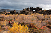 A tourist with red parka and light backpack walks through autumnal trees and bushes toward a lava-rock formation featuring a large hole, Dimmuborgir, near Seyðisfjörðdur, Eastern Iceland, Europe