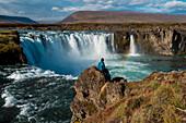 A tourist sits on a rock promontory, viewing the 12 meter high Goðafoss (Waterfall of the Gods), near Seyðisfjörðdur, Eastern Iceland, Europe