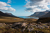 Rocky landscape opening toward the mountainous Seyðisfjörðdur fjord, near Seyðisfjörðdur, Eastern Iceland, Europe