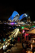 The lit-up Opera House with Opera Bar during the Vivid Festival, Sydney, New South Wales, Australia