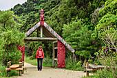 Frau wandert durch Eingangstor des Abel Tasman Coastal Track, Abel Tasman Coastal Track, Great Walks, Abel Tasman Nationalpark, Tasman, Südinsel, Neuseeland