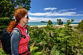 Frau beim Wandern blickt auf Meeresbucht, Abel Tasman Coastal Track, Great Walks, Abel Tasman Nationalpark, Tasman, Südinsel, Neuseeland